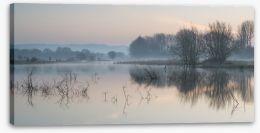 Sunrise glow over misty lake